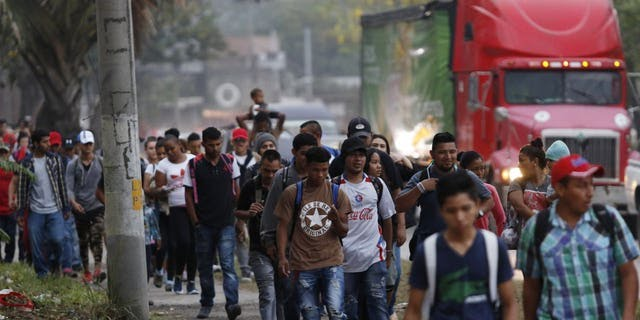 Migrants walk along a highway as a new caravan of several hundred people sets off from San Pedro Sula, Honduras, shortly after dawn on Wednesday, April 10, 2019, in hopes of reaching the distant United States.