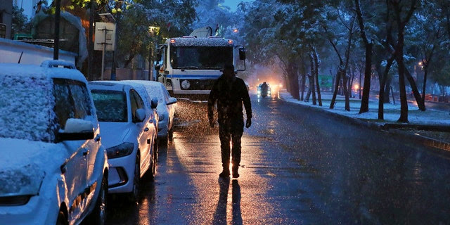 A man walks on a road while it snows in Baghdad, Iraq, Tuesday, Feb. 11, 2020.